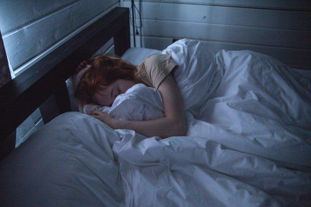 Žena ležiaca na posteli zababušená v perinách