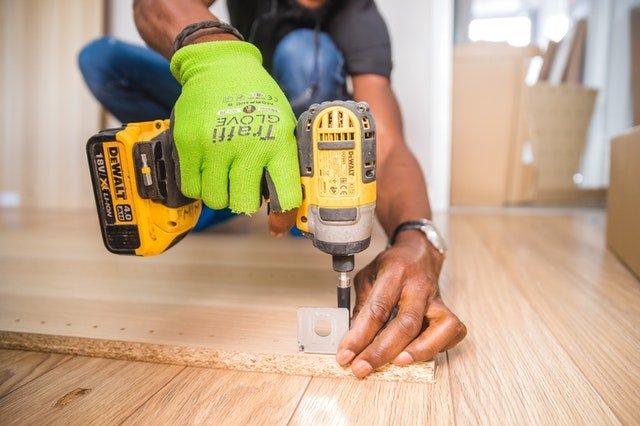 Muž s vŕtačkou v ruke pracuje v interiéri