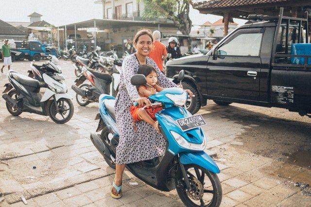 Žena na motorke má pred sebou dieťa bez prilby