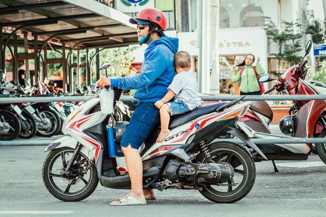Muž s dieťaťom na motorke v meste