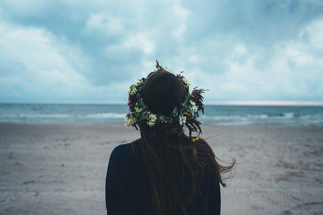 Žena s vencom z kvetov na vlasoch stojí podvečer na pláži a pozerá na more
