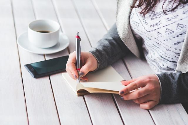 Žena v bielom tričku sedí pri bielom stole a píše na papier