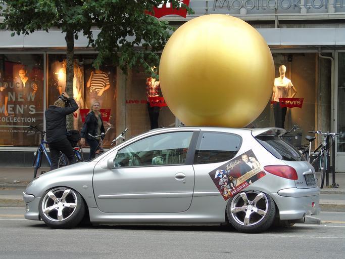 Strieborný Peugeot stojí pred obchodom.jpg