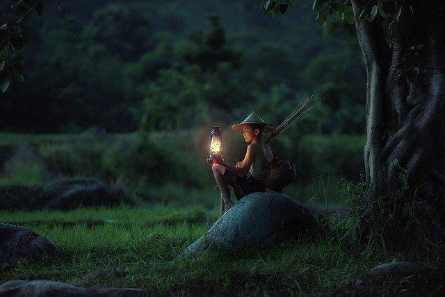 Dieťa sedí na kameni pri strome a v ruke drží zapálený lampáš.jpg