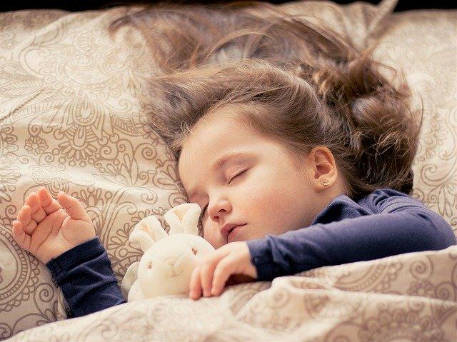 Dievčatko s dlhými vlasmi spí s medvedíkom v posteli pri svetle.jpg